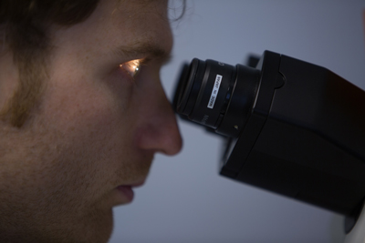 James McConnell looking through a microscope