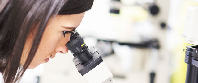 Research we're funding in Manchester - Image of a female scientist looking in a microscope