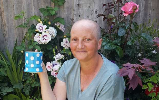 Abi, a smiley woman with a shaved head and a summer tan, poses in front of the flowers in her garden