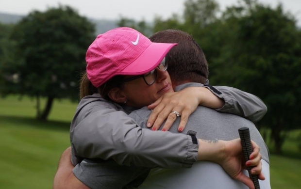 Abigail, a young woman in a pink cap, embraces her husband while holding a golf club