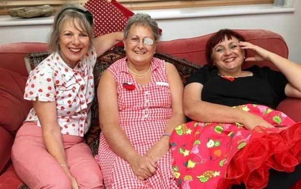 Carol, an older lady with cropped grey hair, sits on a couch between her two sisters. She is wearing a red and white gingham dress.