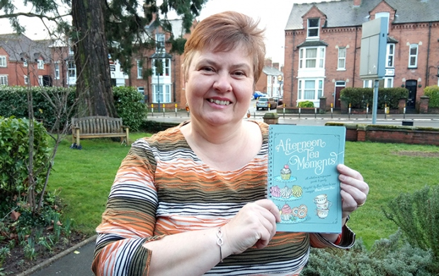 Jane, who has light cropped hair, holds up her recipe book