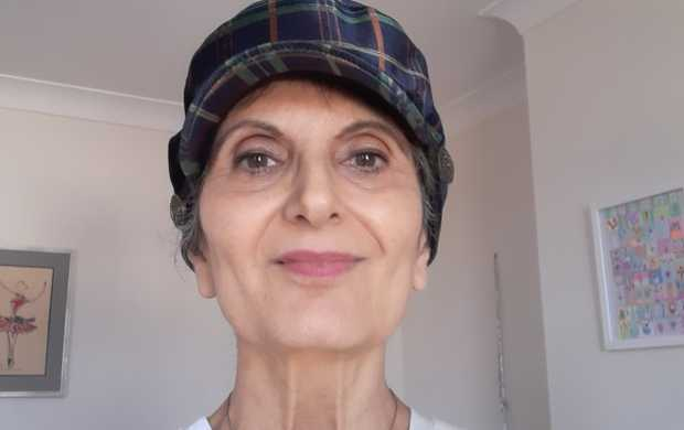 Aliya, who has pale brown skin and brown eyes, smiles while wearing a blue hat