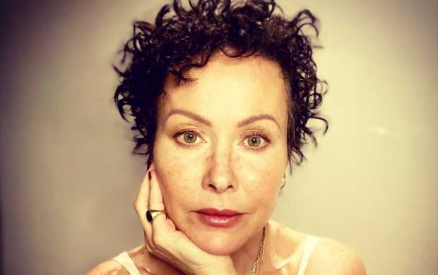 Amanda, a white woman with short curly hair and freckles, looks straight into the camera