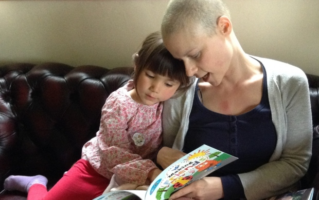 Ann, whose head is shaved, reads a book to her daughter