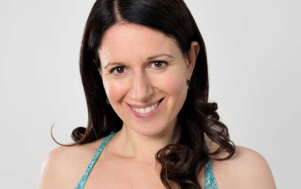 Annabel, who has dark brown hair and eyes, smiles while wearing a blue strappy top