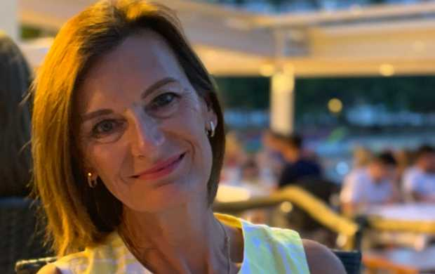 Anne, a white woman with shoulder-length brown hair, smiles while sitting outside at a restaurant in the evening