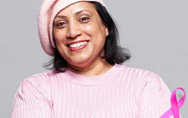 Bal, an Asian woman with short black hair, wears pink in support of breast cancer awareness