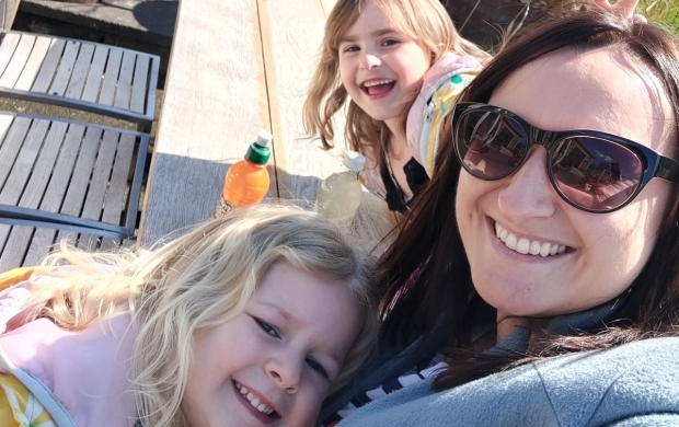 Beth, who has dark hair and wears sunglasses, smiles with her two young daughters