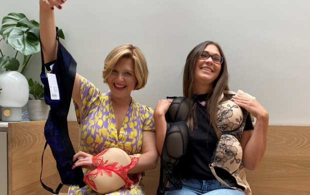 The 'bra sisters', Kate and Sarah, sit side by side and laugh while holding up a number of bras
