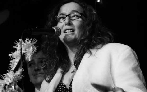 A black and white image of Catrina, a white woman with curly hair and glasses, delivering a speech at a microphone
