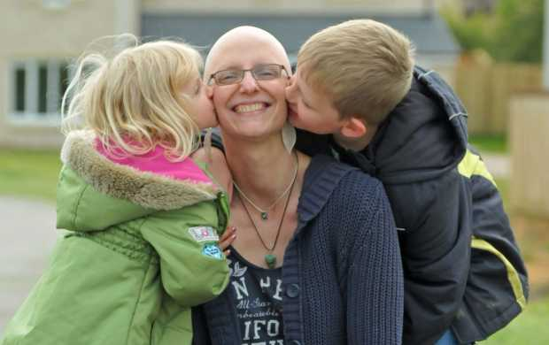 Elke, who has no hair due to chemotherapy, smiles while her children stand either side of her and kiss her cheeks