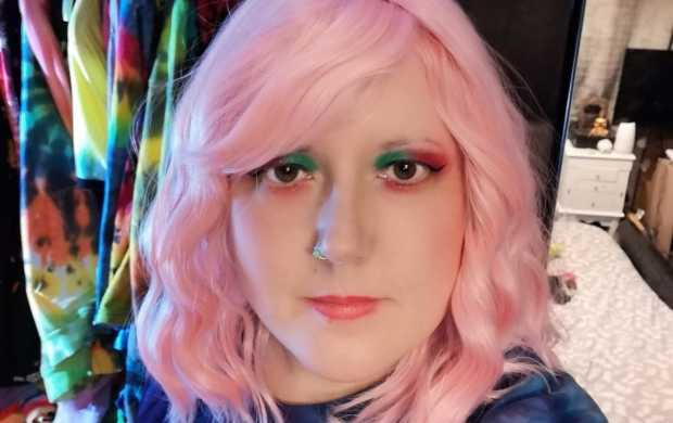 Emma, a young white woman, wears a light pink wig and has colourful eyeshadow