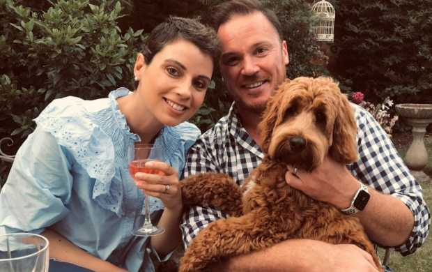 Em, whose hair short following chemotherapy, smiles with her husband and their dog
