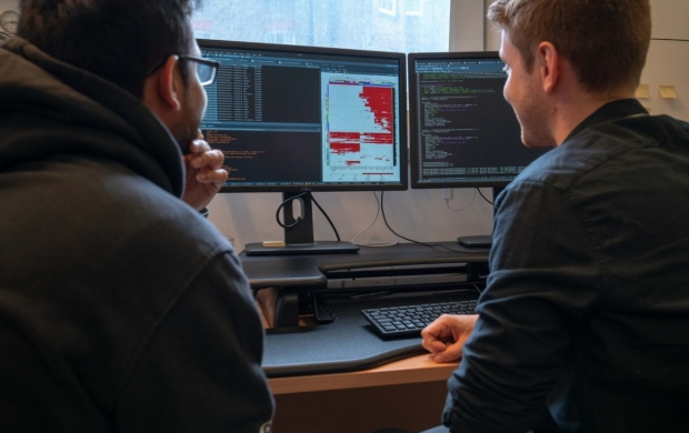 Two men look at research results on a computer screen