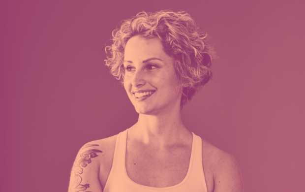 Fran, a young white woman with short, curly hair, smiles and looks off to one side. She wears a tank top which shows tattoos on her right arm.