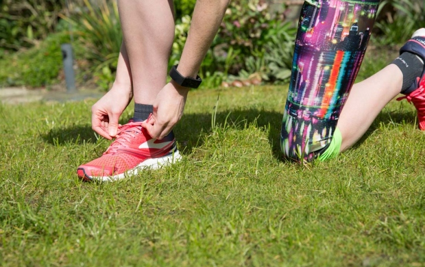 A Breast Cancer Care runner ties her shoe laces in preparation