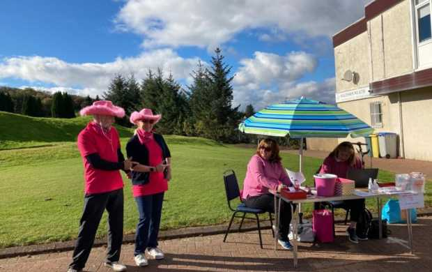 A man and a woman dressed in pink point to a table of Breast Cancer Now supporters, also in pink, as they raise money on a golf course