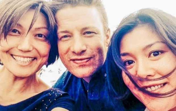 Irene and Yuki, both Asian women with short brown hair, pose for a picture with Jamie Oliver