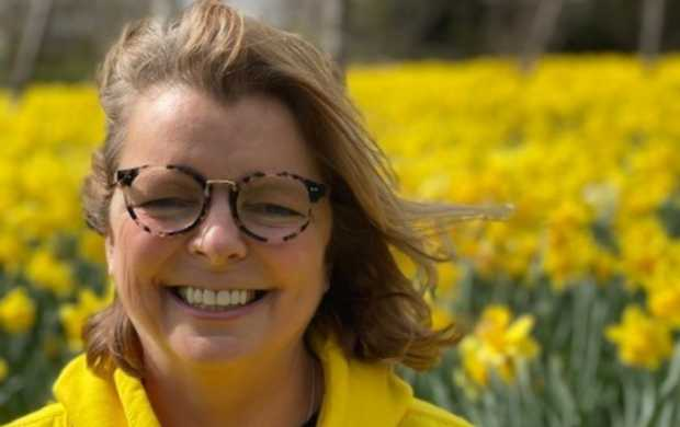 Jen, a white woman with mid-length blonde hair and round glasses, smiles in a field of daffodils while wearing a yellow hoodie