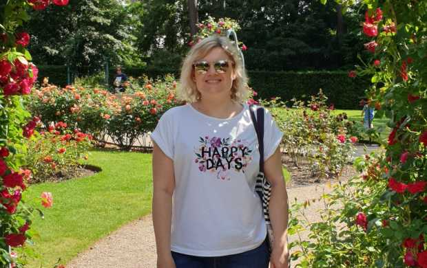 Jo, a young white woman with blonde hair, stands in a beautiful garden surrounded by flowers