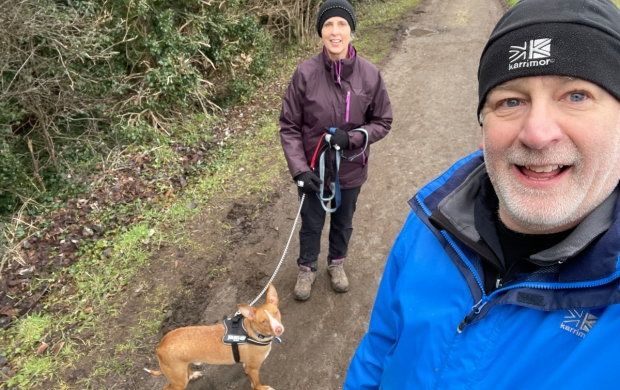 Johnny, a white man with silver stubble, takes a wintery walk with his partner and their dog