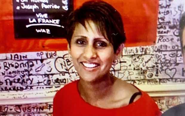 Kully, a woman with short dark hair, smiles in a restaurant