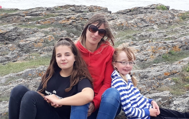Natasha, who is wearing sunglasses and a bright red hoodie, sits outside with her two daughters