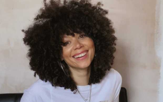 Nina, a slim biracial woman with big curly hair, smiles broadly for the camera