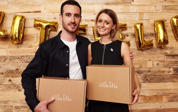 Oa, who is white and has short, dark blonde hair, holds up a littlelifts box beside her husband, Greg. Both of them are smiling.
