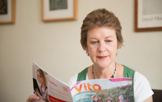 Woman reading Breast Cancer Care's Vita magazine