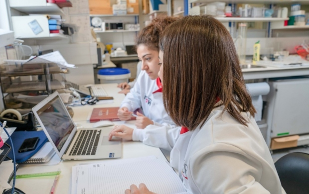 two female researchers sitting at a desk in a laboratory