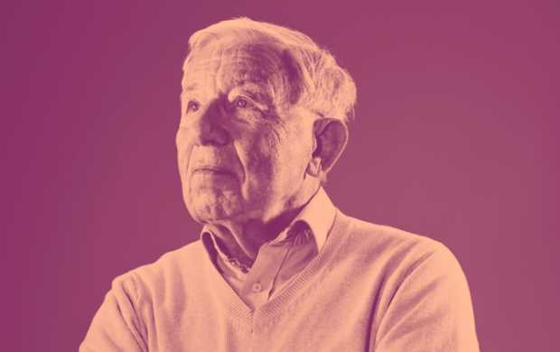 Roger, an older white man with short white hair, looks thoughtful as he poses in a smart shirt and jumper.