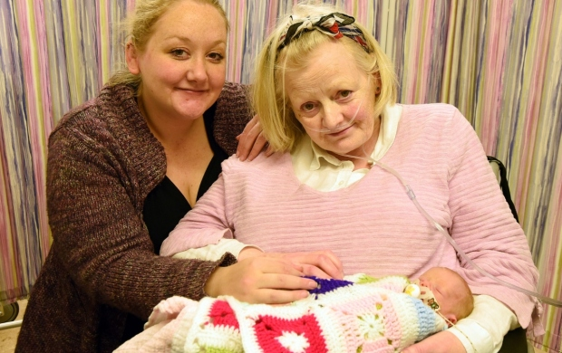 Shirley, an elderly lady with grey-blonde hair, cradles her infant granddaughter while her daughter sits next to her.