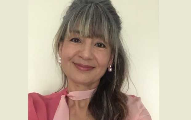 Sue, an Asian woman with long grey hair, smiles while wearing a beautiful pink top and pearl earrings