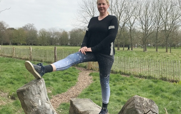 Susan stretches one leg while standing on a fallen tree
