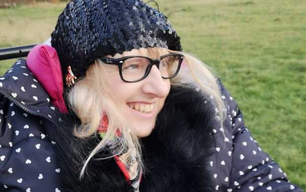 Suzanne, a smiley white woman with blonde hair, wears a sparkly winter hat, blue puffy coat and glasses.