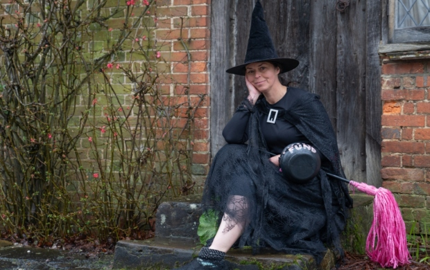 Judy, a white woman with dark hair, sits on a stone step in her witch costume
