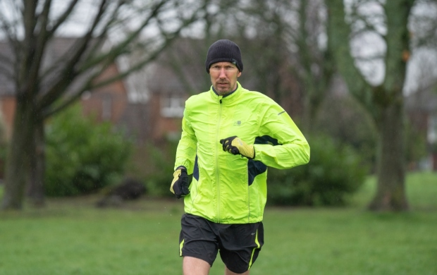 Mark, who is wearing florescent running gear, jogs through a park