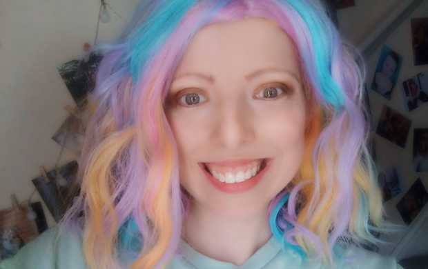 Tish, a young person with blue, yellow and purple hair