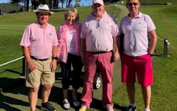 Four golfers, all dressed in pink, stand together