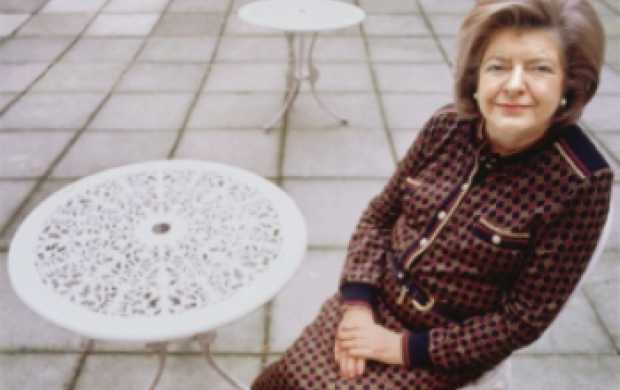 Verite, an older white woman with neat brown hair, sits outside wearing a smart suit