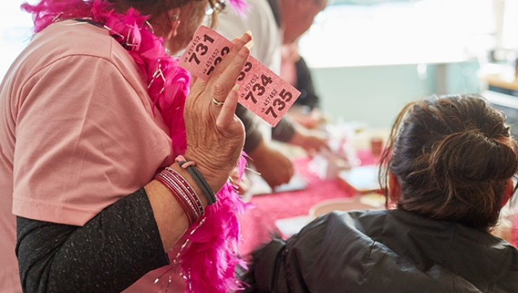 A woman dressed in pink holds a strip of raffle tickets