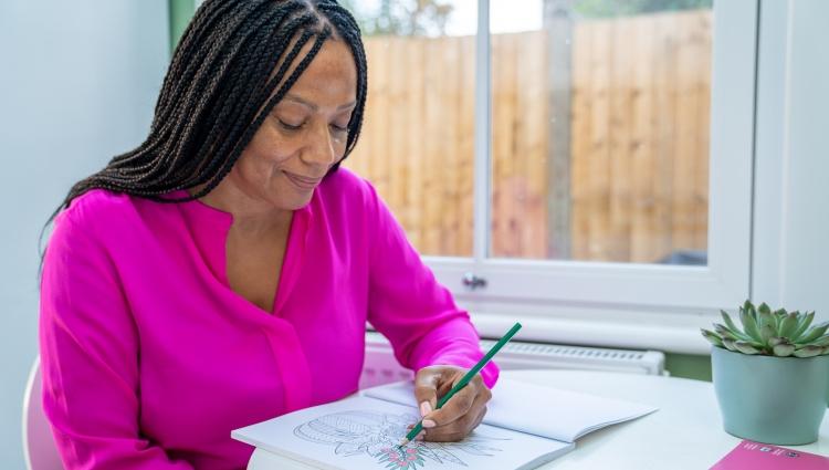 Woman using a colouring book near a window