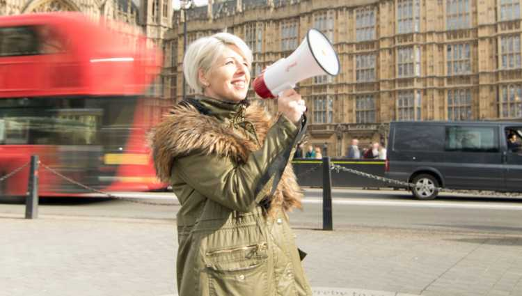 A woman stands near a busy London road with a megaphone