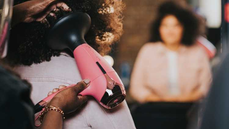 A hair stylist using a pink ghd hairdryer on a person with curly brown afro hair