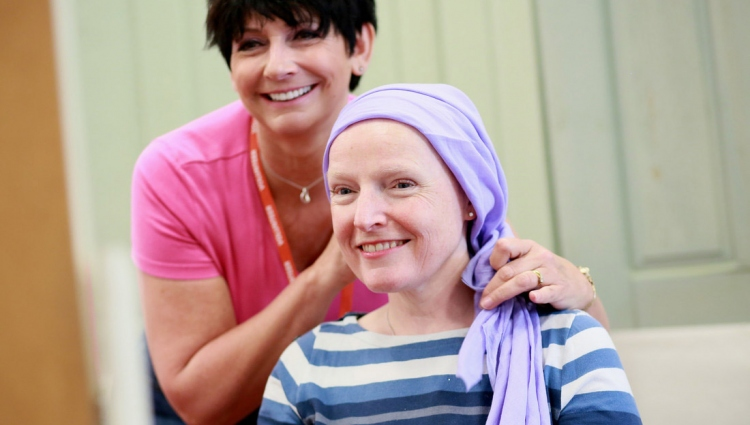 A Breast Cancer Care support worker helps a woman ties a scarf around her head to cover her hair loss.