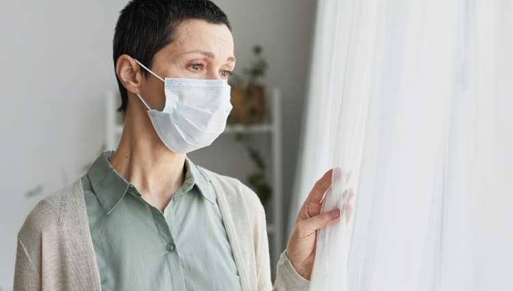 Women wearing face mask looking out of the window