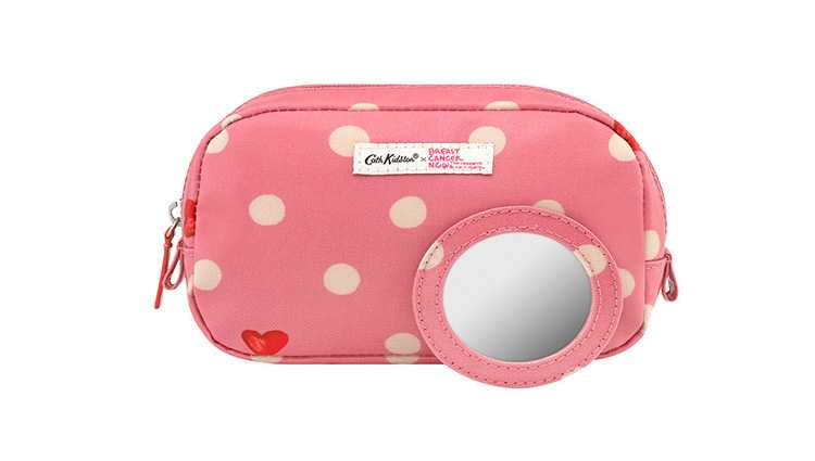 Pink spotted cosmetic case with a small mirror in front of it
