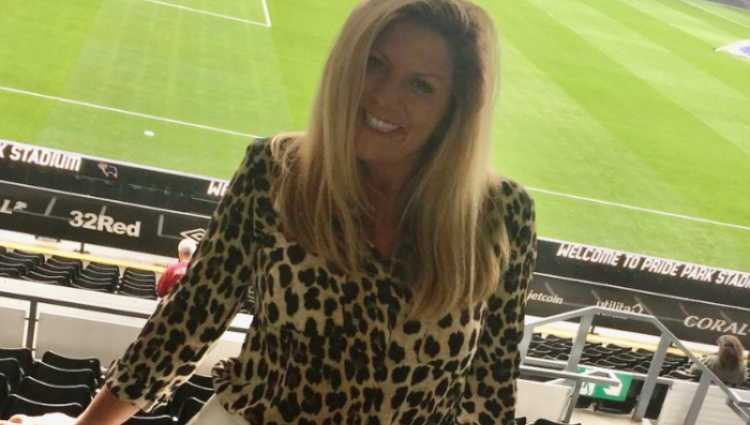 Jacqui, who has long blonde hair and leopard print top, smiles widely while standing in a football stadium